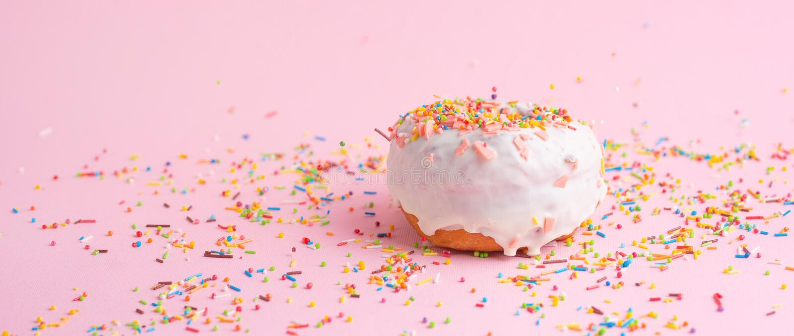 Sprinkle pink donut. on a pink background with space for design. Banner. Sprinkles cake calories eat sugar colorful dough iced pastry food dessert doughnut royalty free stock photo