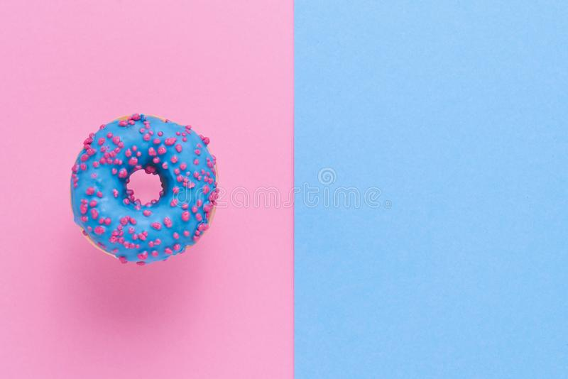 Sprinkled Blue Donut. Glazed sprinkled donut on pink blue background. Top view, copy space royalty free stock images