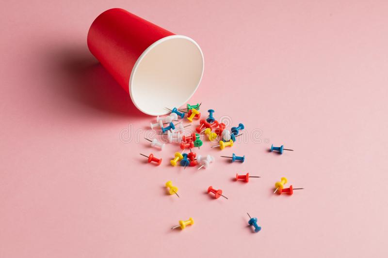 Sprinkled colorful different pins in the open bottle. royalty free stock photo