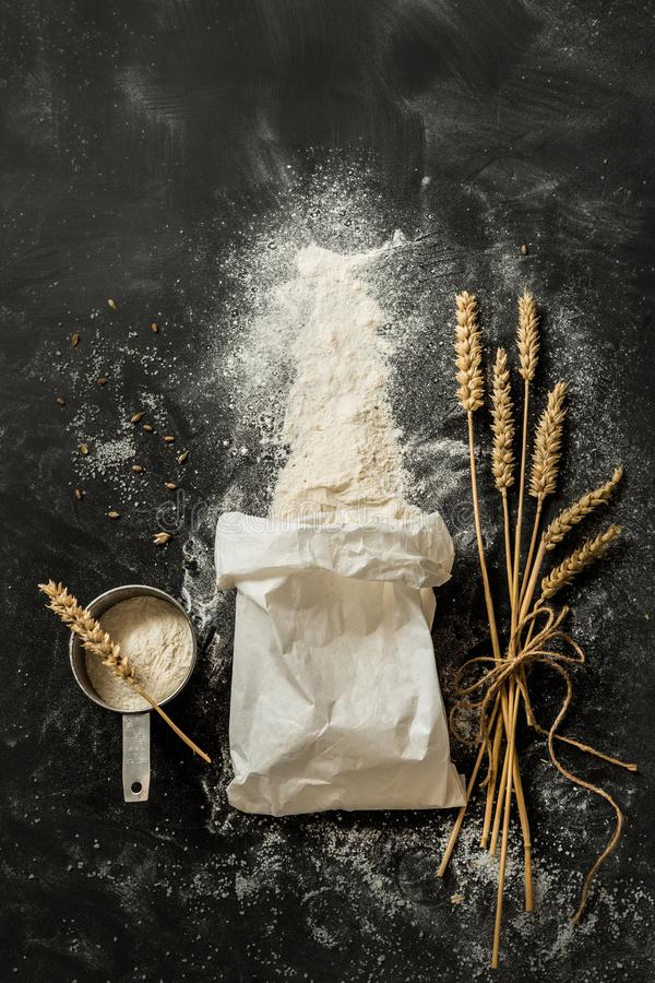 Flour bag, ears of wheat and measuring cup on black. Sprinkled flour coming out from the white paper bag, measuring cup and ears of wheat. Captured from above stock photos