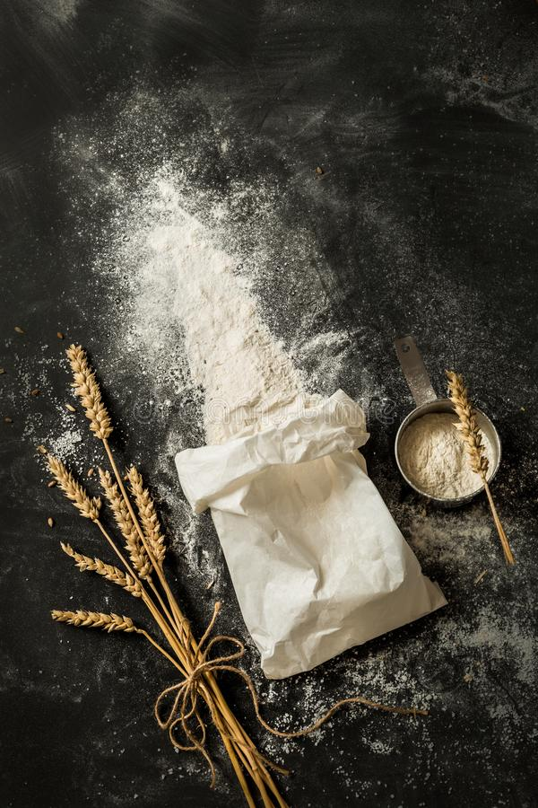 Flour bag, ears of wheat and measuring cup on black. Sprinkled flour coming out from the white paper bag, measuring cup and ears of wheat. Captured from above royalty free stock photography
