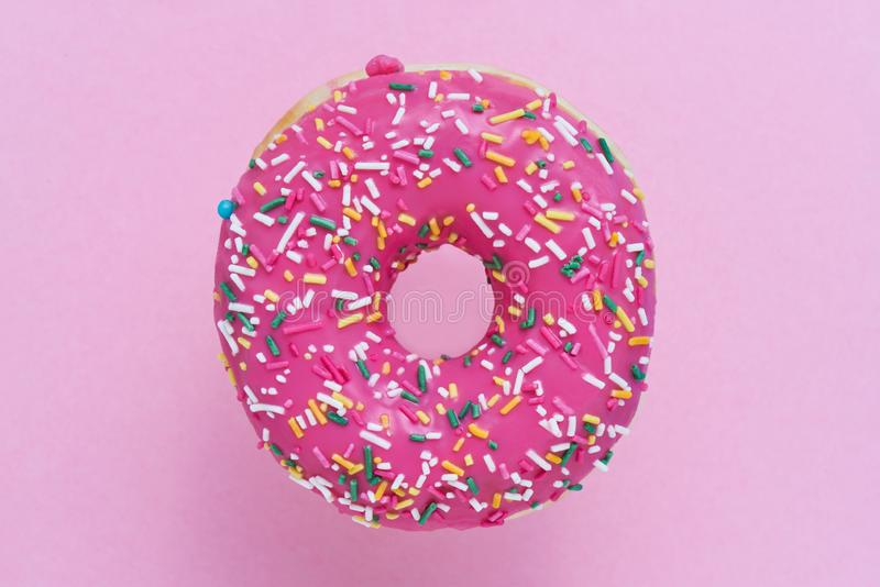 Sprinkled Pink Donut. Glazed sprinkled donut on pink background. Top view, copy space.  stock photos
