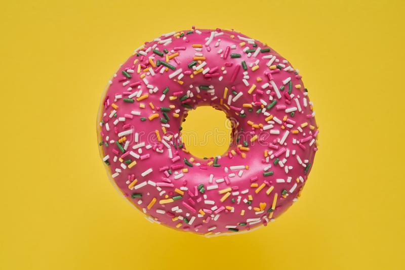 Sprinkled Pink Donut. Glazed sprinkled donut on yellow background. Top view, copy space stock photography