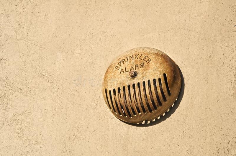 Sprinkler Alarm. Rusted sprinkler alarm on building wall outside stock images