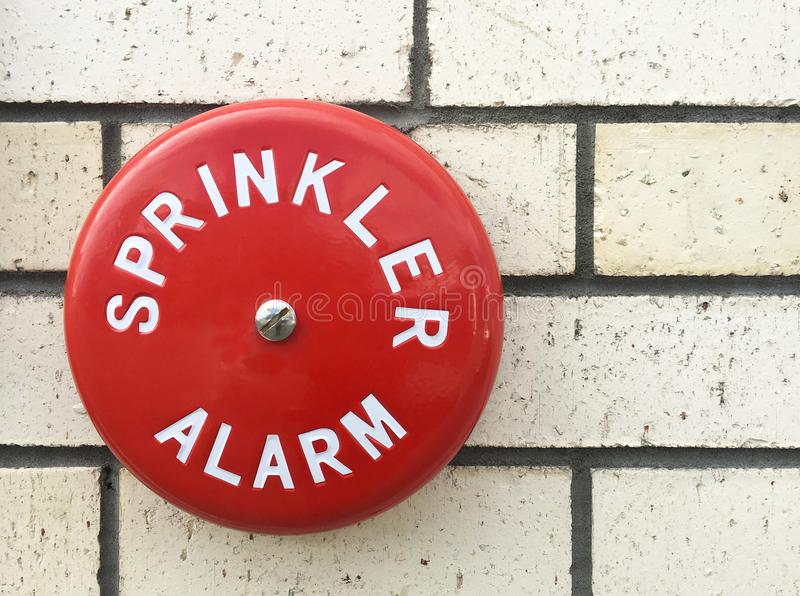 Sprinkler alarm bell on a building brick wall. Fire sprinkler system stock photos