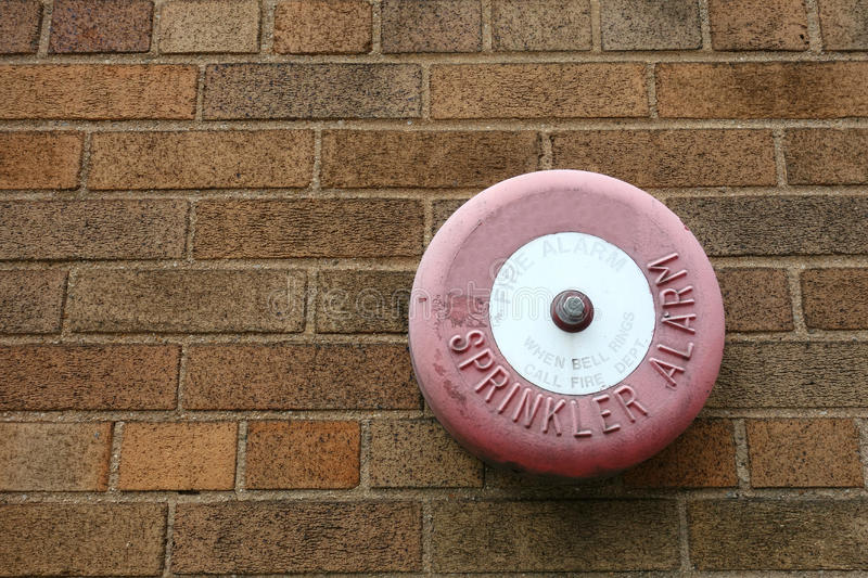 Sprinkler Alarm. A sprinkler alarm mounted on a brick wall, that says When bell rings, call fire department royalty free stock image