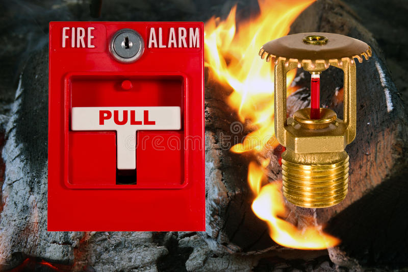 Sprinkler head and pull station. Fire alarm pull station and sprinkler valve over a flame background royalty free stock photo