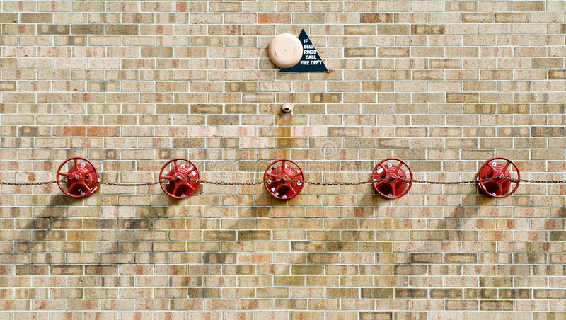 Sprinkler System. Fire alarm with sprinkler system valves on outside of building stock photo