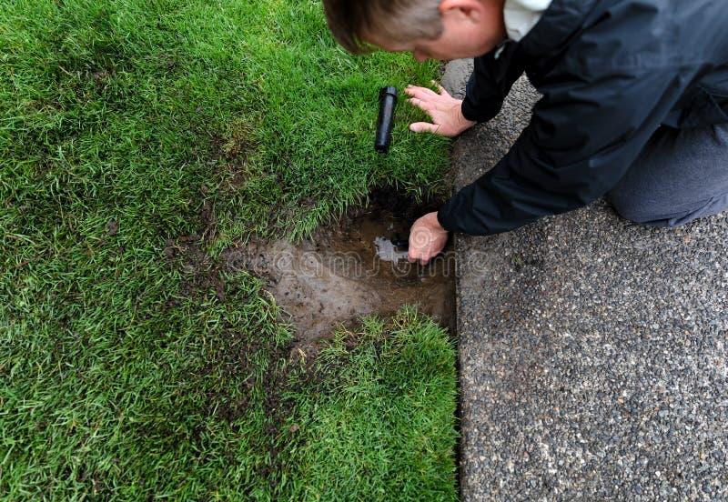 Sprinkleranläggning som repareras av den mogna mannen med bevattningdelar som lägger på jordning royaltyfri fotografi