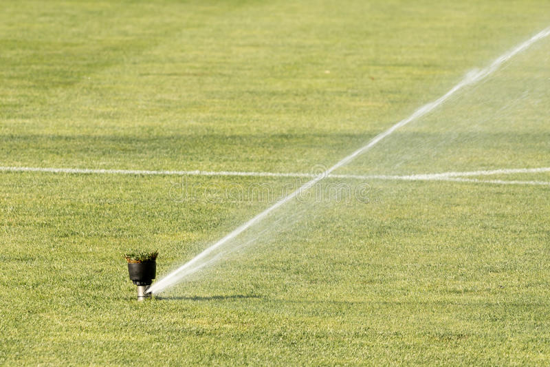 Sprinkleranlage, die an frischem grünem Gras auf arbeitet Stadion des Fußballs (Fußball) stockfotografie