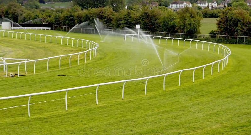 Sprinklers on racecourse. Sprinklers watering racecourse rails corner stock photos