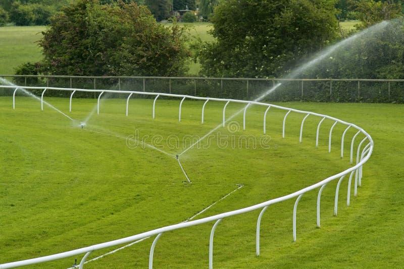 Sprinklers on racecourse. Sprinklers watering racecourse rails corner royalty free stock photography