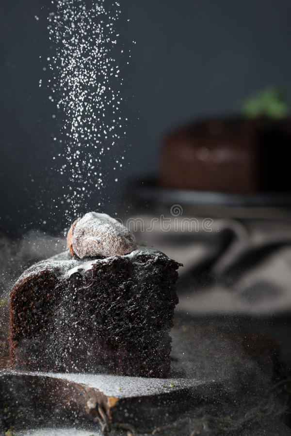 Sprinkling of dark chocolate cake with powdered sugar. Wooden vintage tray with chains stock photo