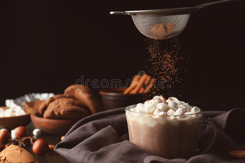 Sprinkling of hot drink with cacao powder on dark background royalty free stock images