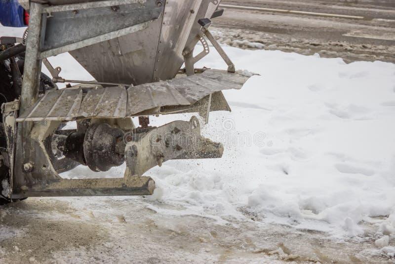 Sprinkling salt on a sidewalk after snowfall. Machine sprinkling salt on a sidewalk after snowfall royalty free stock photography