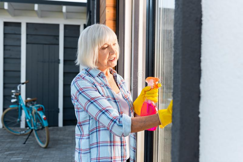 Blonde-haired retired woman sprinkling water while washing windows royalty free stock photos