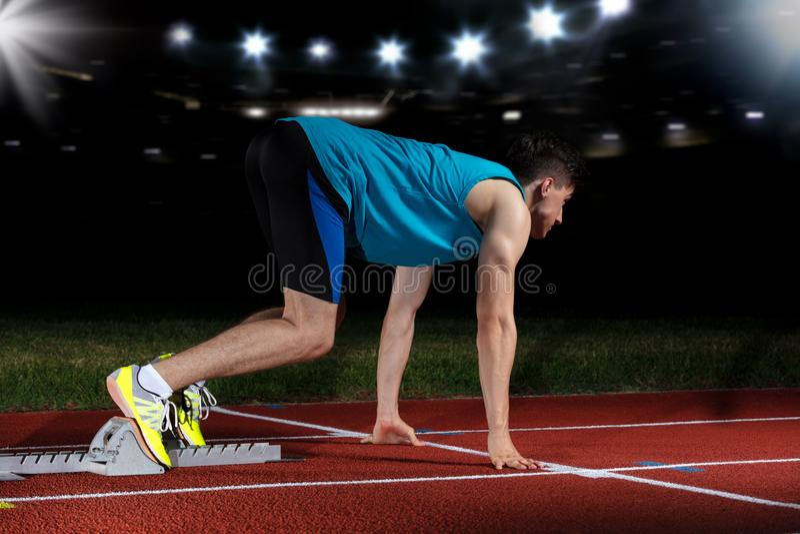 Sprinter που αφήνει τους αρχικούς φραγμούς στην τρέχοντας διαδρομή μπροστά από το μεγάλο σύγχρονο στάδιο με τα φω'τα explosive st στοκ φωτογραφία