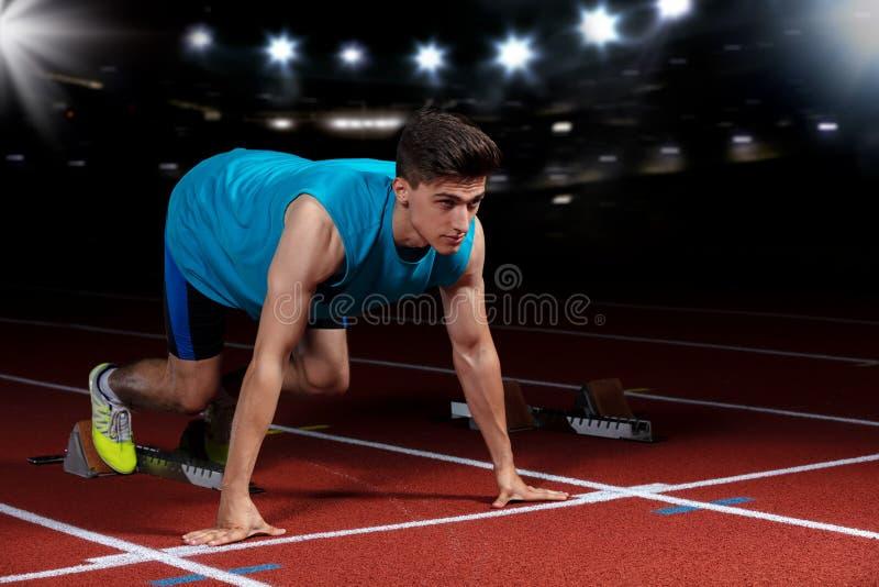 Sprinter που αφήνει τους αρχικούς φραγμούς στην τρέχοντας διαδρομή μπροστά από το μεγάλο σύγχρονο στάδιο με τα φω'τα explosive st στοκ φωτογραφίες με δικαίωμα ελεύθερης χρήσης