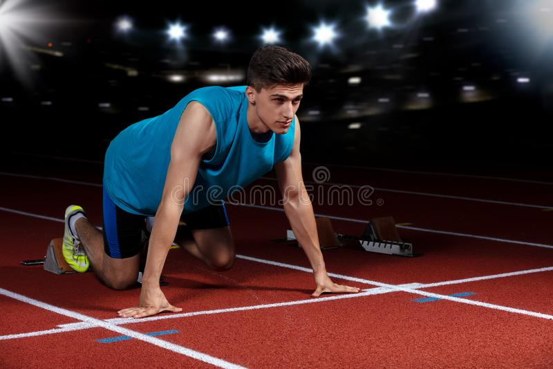 Sprinter που αφήνει τους αρχικούς φραγμούς στην τρέχοντας διαδρομή μπροστά από το μεγάλο σύγχρονο στάδιο με τα φω'τα explosive st στοκ εικόνες με δικαίωμα ελεύθερης χρήσης