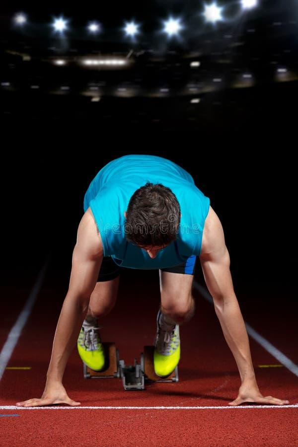 Sprinter που αφήνει τους αρχικούς φραγμούς στην τρέχοντας διαδρομή μπροστά από το μεγάλο σύγχρονο στάδιο με τα φω'τα explosive st στοκ εικόνες