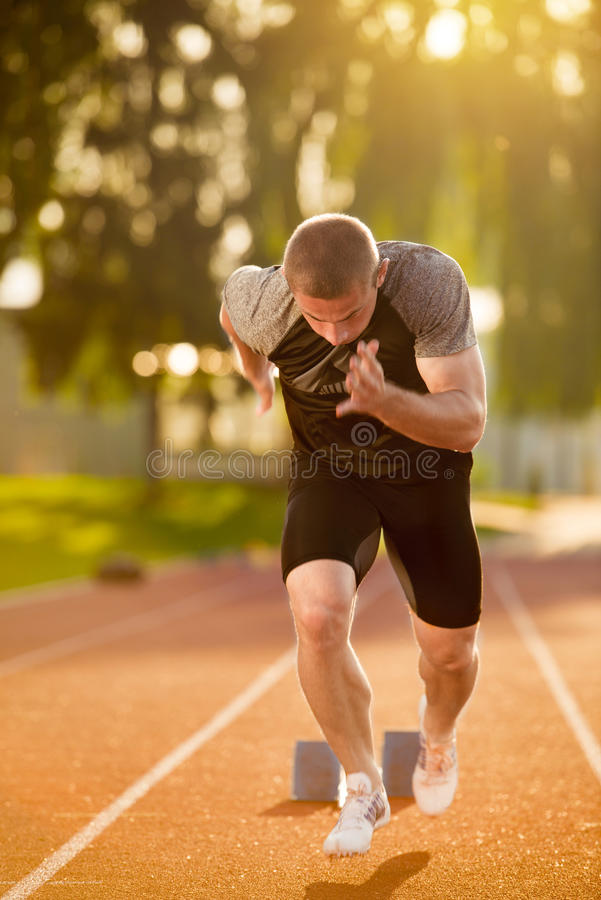 Sprinter που αφήνει τους αρχικούς φραγμούς στην τρέχοντας διαδρομή explosive start στοκ εικόνες