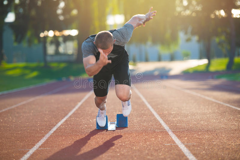 Sprinter που αφήνει τους αρχικούς φραγμούς στην τρέχοντας διαδρομή explosive start στοκ εικόνα