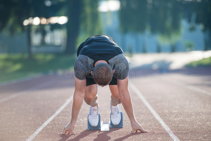 Sprinter που αφήνει τους αρχικούς φραγμούς στην τρέχοντας διαδρομή explosive start στοκ εικόνες με δικαίωμα ελεύθερης χρήσης