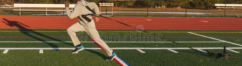Sprinter που τραβά ένα ζυγισμένο έλκηθρο στοκ φωτογραφίες