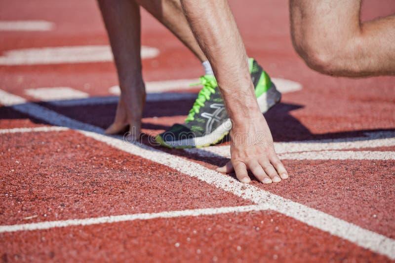 Sprinter στη γραμμή έναρξης λαστιχένιας τρέχοντας πορείας σταδίων στοκ εικόνες