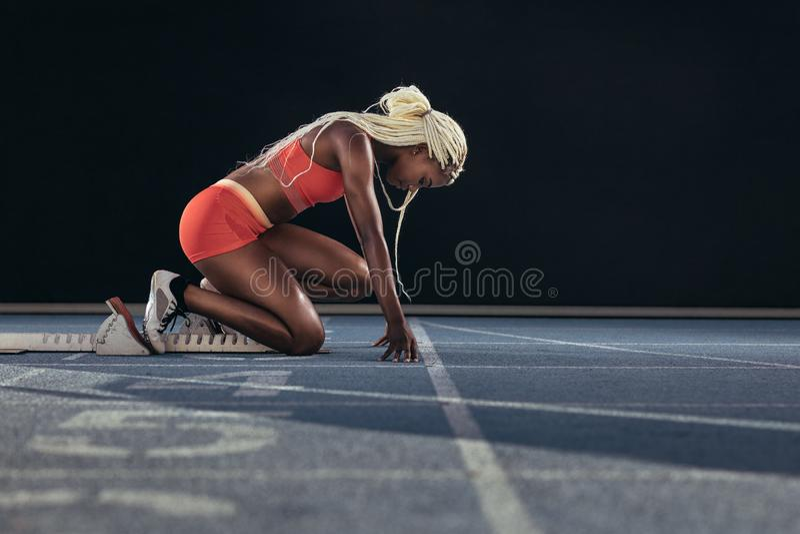 Sprinter χρησιμοποιώντας έναν αρχικό φραγμό για να αρχίσει την ορμή της σε ένα τρέξιμο στοκ εικόνες