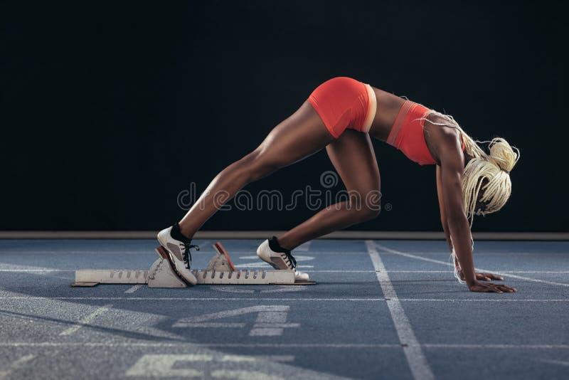 Sprinter che per mezzo di un blocchetto iniziare per iniziare il suo sprint su un funzionamento fotografie stock libere da diritti