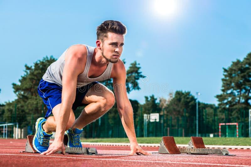 Sprinter d'athlétisme sur le point de départ à la voie de cendre en PS images stock