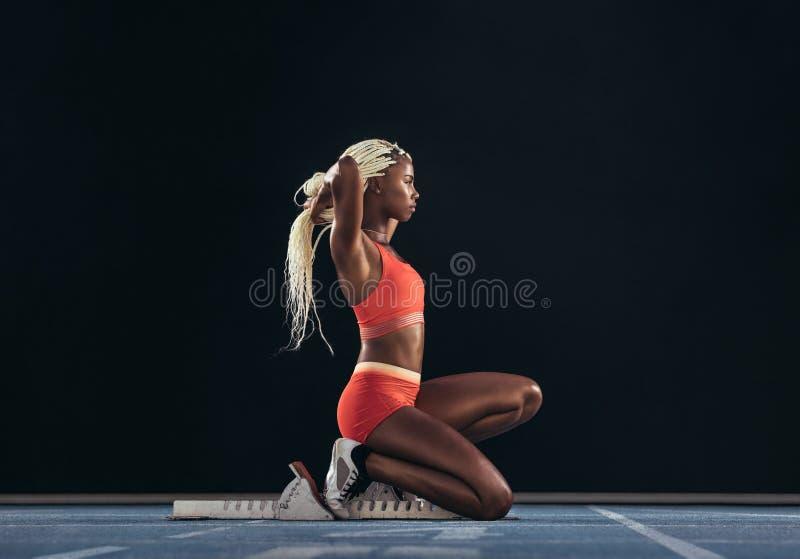 Sprinter della donna che si siede alla linea di inizio su una pista corrente fotografia stock libera da diritti