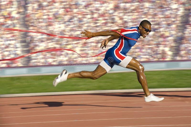Sprinter die de Lijn van de Afwerking kruist stock fotografie
