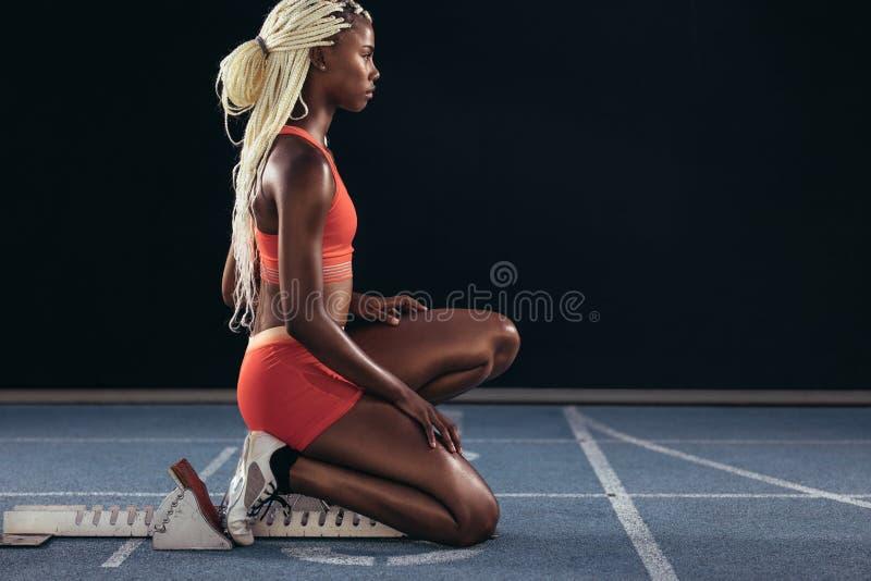 Sprinter die een standpunt betreffende een startblok innemen om haar sprint te beginnen stock fotografie
