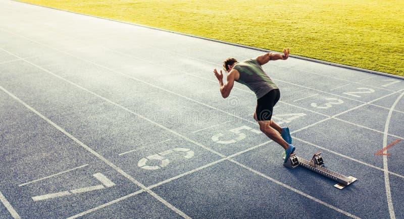 Sprinter die van startblok op renbaan opstijgen stock afbeeldingen