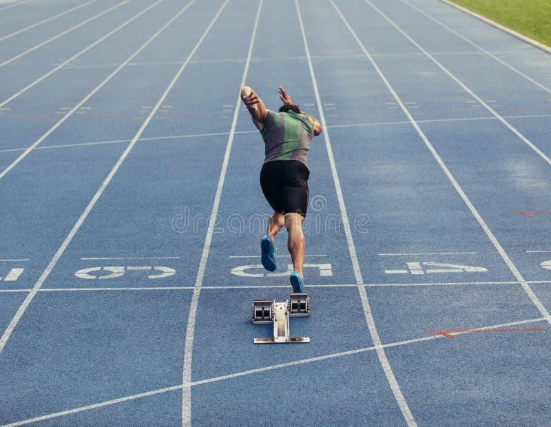 Sprinter die van startblok op spoor opstijgen stock afbeeldingen