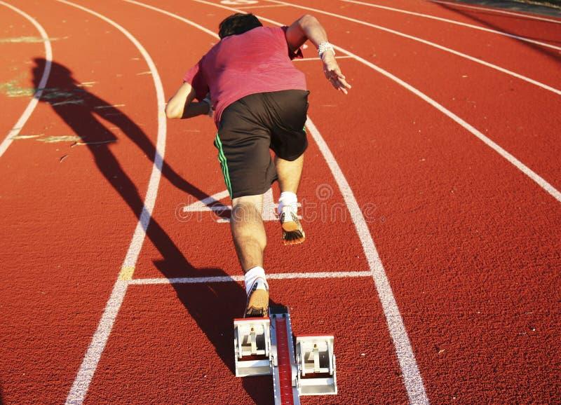 Sprinter hors des blocs à la pratique photographie stock