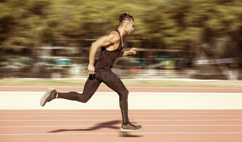 Sprinter leaving starting blocks on the running track. Explosive royalty free stock photography