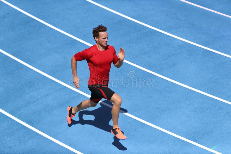 Sprinter man running on blue tracks lanes in track and field stadium in high speed top view. Male athlete runner in intense sprint stock image