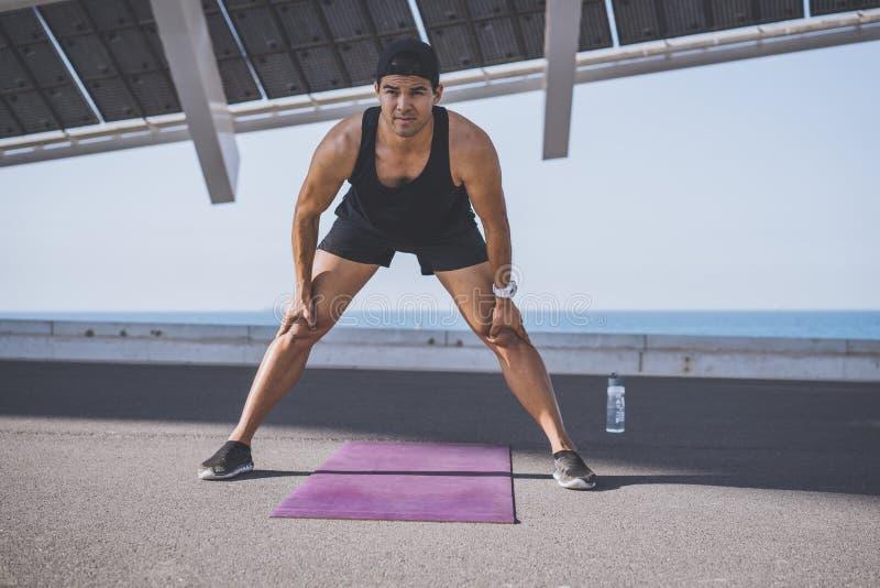 Sprinter masculin musculaire d'athlète faisant étirant l'exercice, s'exerçant dehors, pulsant dehors Style de vie sain photos stock