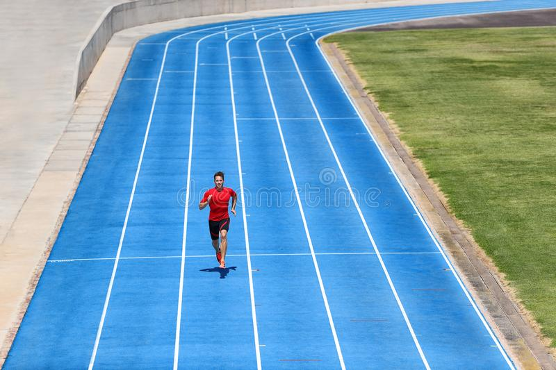 Sprinter runner athlete man sprinting on outdoor track and field running lanes at stadium. Sport and health active training on royalty free stock photos