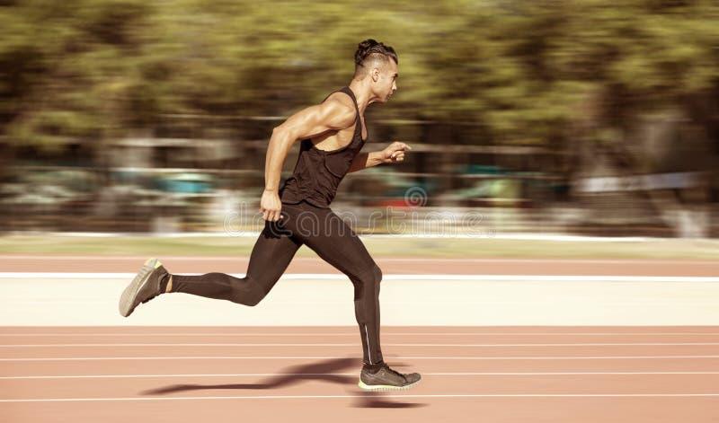 Sprinter som lämnar startgrop på det rinnande spåret explosivt royaltyfri fotografi