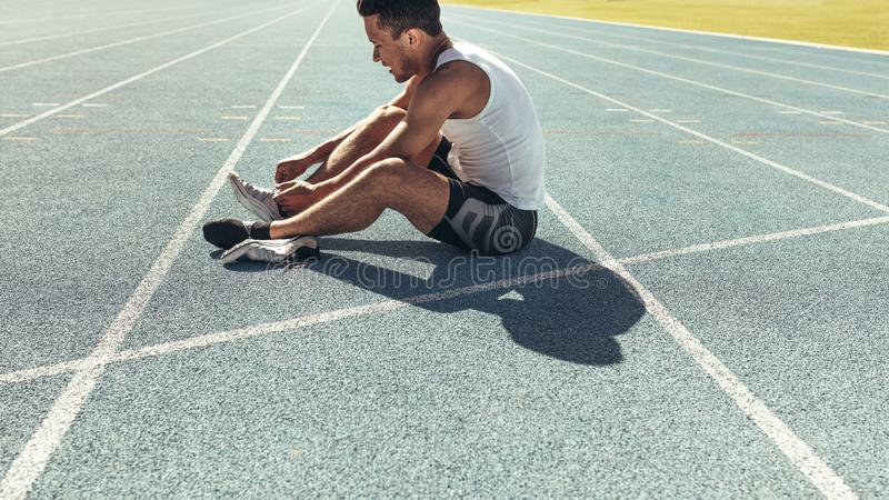 Sprinter tying shoe lace sitting on running track. Athlete sitting on a running track tying shoe lace. Runner sitting on the running track wearing his shoes stock photos