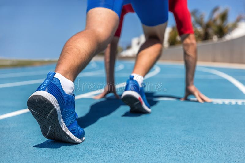 Sprinter waiting for start of race on running tracks at outdoor stadium. Sport and fitness runner man athlete on blue run track. With running shoes stock images