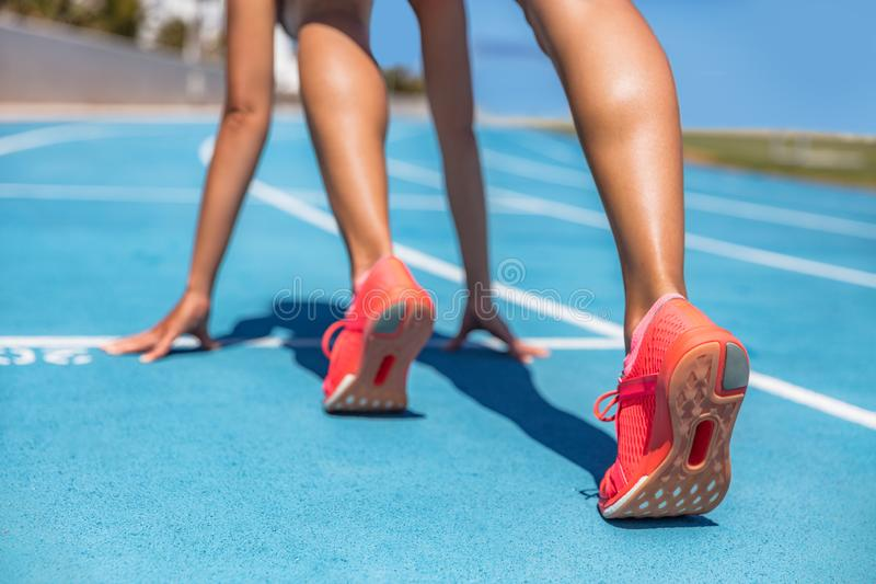 Sprinter waiting for start of race on running tracks at outdoor stadium. Sport and fitness runner woman athlete on blue run track. With orange running shoes stock photography
