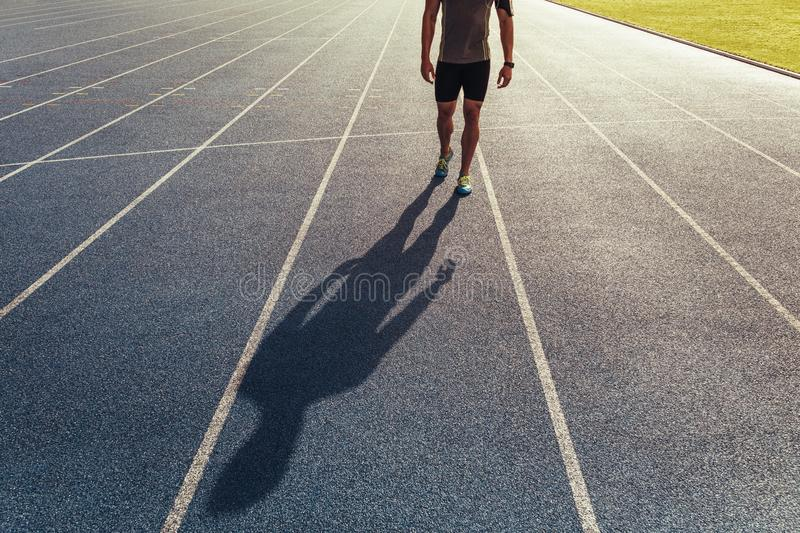 Sprinter walking on running track. Athlete walking on an all-weather running track listening to music. Shadow of a runner walking on the track royalty free stock images