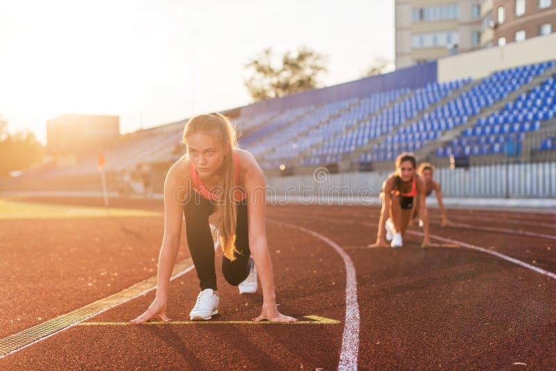 Sprinters γυναικών στην αρχική θέση έτοιμη για τη φυλή στη πίστα αγώνων στοκ εικόνες