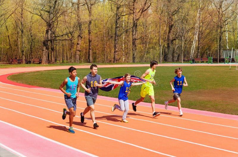 Sprinters adolescents de voie courant avec le drapeau britannique image libre de droits