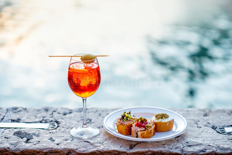 Spritz Aperol with cicchetti. Spritz Aperol drink with venetian traditional snacks cicchetti on the water chanal background in Venice. Traditioanal italian royalty free stock photography